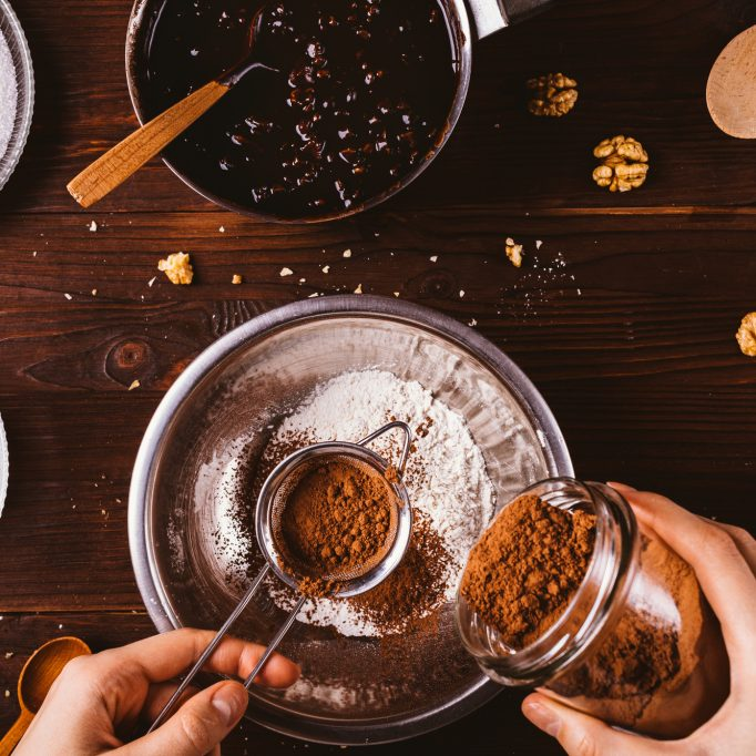 Female's hands sift cocoa powder into bowl with flour to make dough for chocolate brownie cake, top view on dark wooden table.